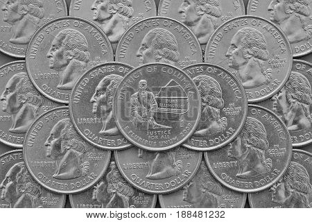District of Columbia State and coins of USA. Pile of the US quarter coins with George Washington and on the top a quarter of District of Columbia State.