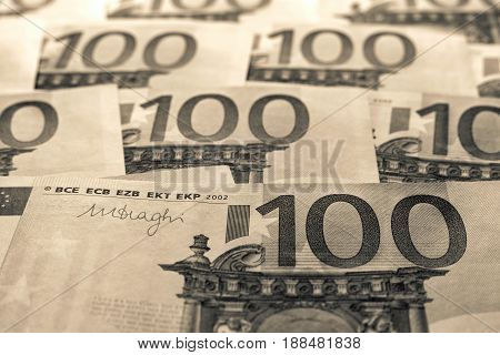 abstract unsharp background a collage from money and currency or from paper banknotes in hundred euros closeup of color sepia