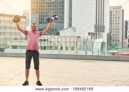Young man holding two gyroscooters. Guy in the city smiling. Free hoverboard giveaway.