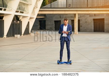 Businessman on hoverboard. Man with tablet outdoors. Business and new technologies.