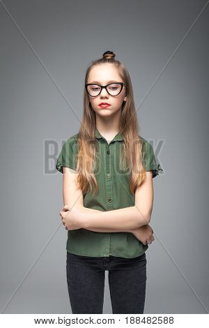 Portrait of young sad spectacled girl over gray background. woman dressed in green T-shirt. red lips.