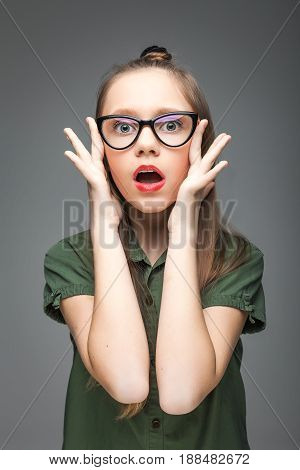 Portrait of young surprised spectacled girl over gray background. woman dressed in green T-shirt. red lips.