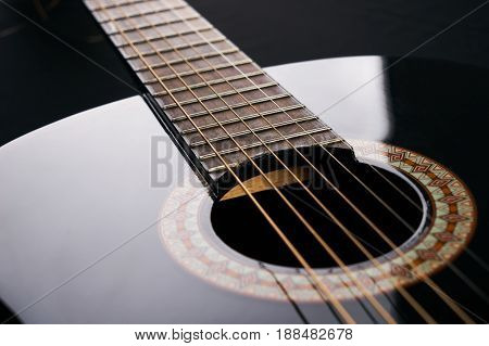 Part of a black Six-string classical acoustic guitar on black background.
