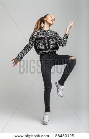 activity and fitness concept - teenage girl in black t-shirt, jeans and white moccasins jumping high and posing