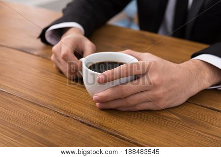 Businessman coffee break closeup, hands with americano cup on wood table