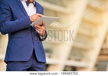 Man in suit using tablet. Businessman with a gadget. Business information systems.