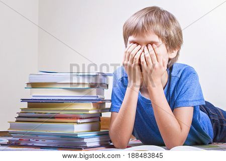 Tired kid with stack of colorful books. Close up