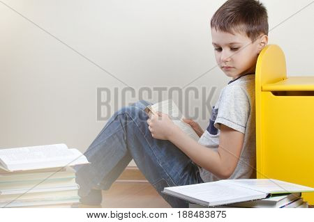 Boy reading books at home. Education, childhood, school concept
