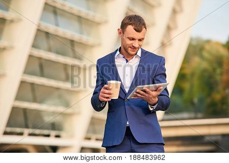 Businessman holding tablet and cup. Young man in suit outdoors. Breaks boost work productivity.