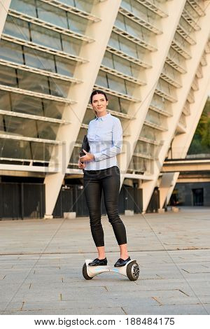 Businesswoman on hoverboard. Female holding a folder. Modern business and laws.