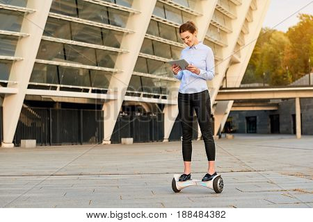 Woman on hoverboard with tablet. Young businesswoman smiling outdoors. Business on the go.