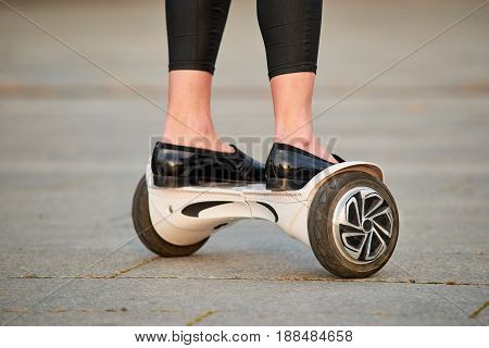 Legs on gyroscooter, close up. Person riding white hoverboard,