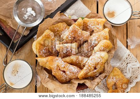 Sweet crisp pastry Angel wings with powdered sugar for coffee