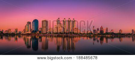Cityscape image of Benchakitti Park at sunset in Bangkok Thailand.