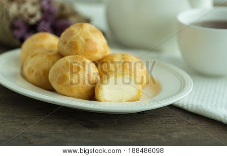 Homemade cream puffs or eclaires filled with vanilla custard cream.Golden choux cream on white plate put on rustic wood table. Cream puffs serve with tea or coffee. Cream puffs or choux cream or eclairs. French pastry : cream puffs or choux cream.