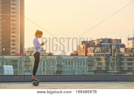 Woman on hoverboard holding tablet. Female on city background.