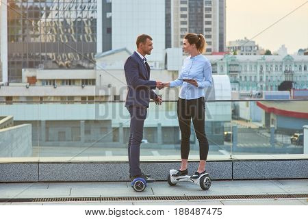 Businessman and woman shaking hands. People on hoverboards, city background. Building work relationships.