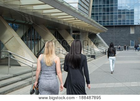 Two girls blonde and brunette with long hair walking on the street near the business center. The girl is tired and carries the shoes in his hand, from behind.