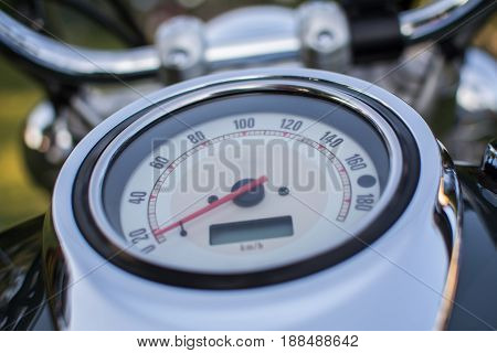 Motorcycle speedometer photographed outdoors, from close distance