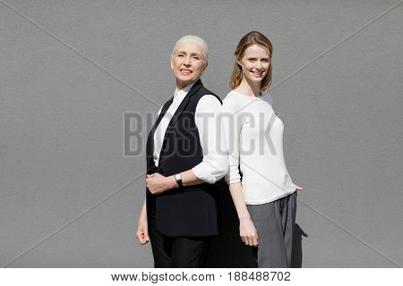 Two Beautiful Smiling Women Standing Back Ro Back Isolated On Grey