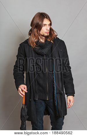 Portrait of handsome fashionable man wearing black coat and scarf holding umbrella. Young guy posing in studio. Winter or autumn fashion.