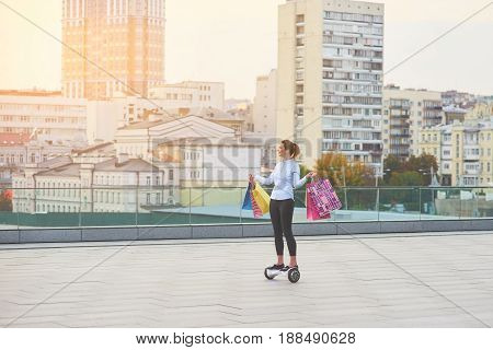 Woman with shopping bags. Female on hoverboard, city background. Best outlet stores.
