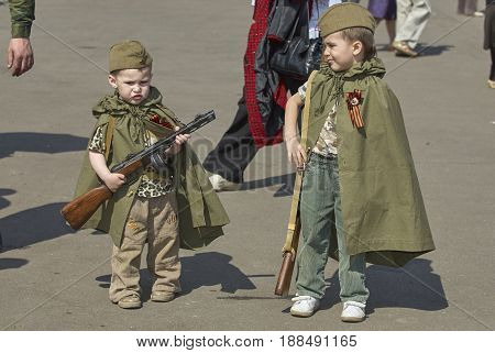 MOSCOW, MAY 9, 2010: Two boys brothers in green USSR WWII uniform with soviet machine gun, rifle on celebration of Great victory 65th anniversary in Gorky Park. USSR  9 May Victory day