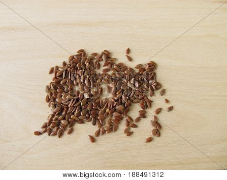 Healthy linseeds or flaxseeds on wooden board