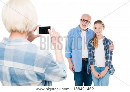 Grandmother Taking Photo Of Grandfather And Grandchild Isolated On White