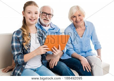 Grandfather, Grandmother And Grandchild Using Digital Tablet And Sitting On Sofa Isolated On White