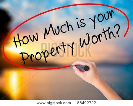 Women Hand Writing How Much Is Your Property Worth? With Black Marker On Visual Screen