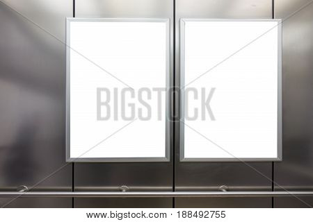 Mock up. Two vertical poster media template frame hanging on the wall in elevator lift
