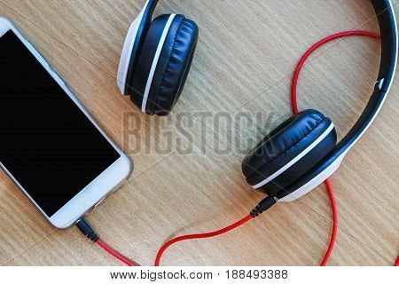 Headphones on wood background Concept listen to music from smartphone