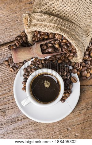 rustic bag full of coffee beans with wooden and cup of coffee on wooden table