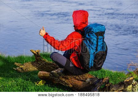 Tourist with a backpack, resting on a log near the river and showing a thumbs-up. Hiking tours, back view