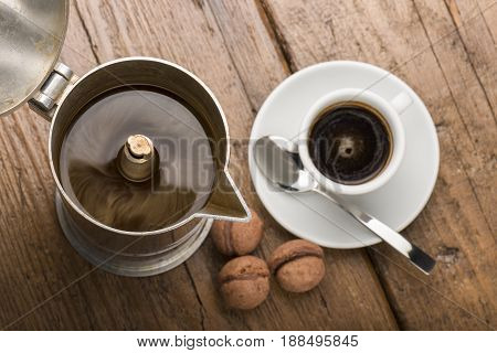 coffeepot and cup of coffee with chocolate cookies on wooden table