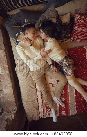 Young couple staying at home together on holiday evening and lying on bed with christmas bed linen. Young lovers ib cute pullovers hugging and relaxing. Top view