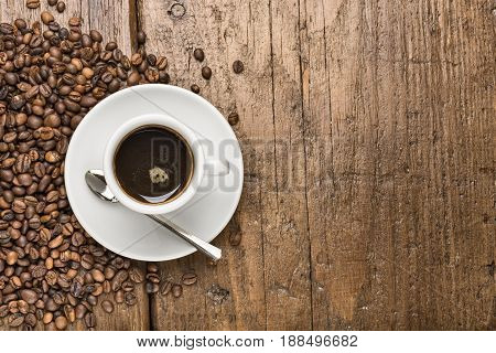 cup of coffee with coffee beans on wooden table