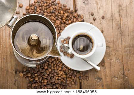coffeepot and cup of coffee with coffee beans on wooden table