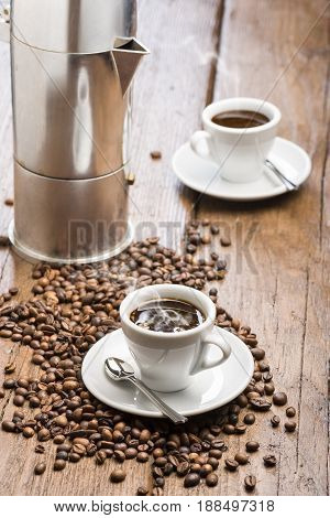 cup of coffee with coffeepot and coffee beans on wooden table