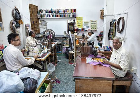 Muscat Oman - March 15 2017: Indian man working as a tailor using an old fashioned sewing machine at a tailor shop in Muscat Oman