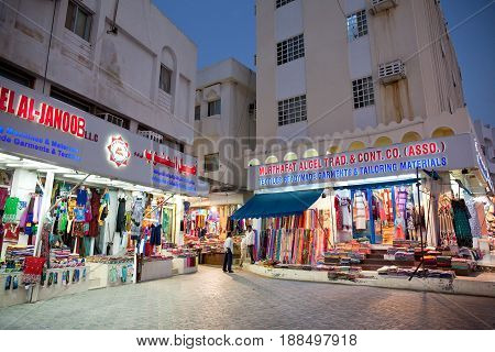 Muscat Oman - March 15 2017: Colorful rolls of cloth and dresses seen in front of a tailor shop at down in Muscat Oman in the Middle East
