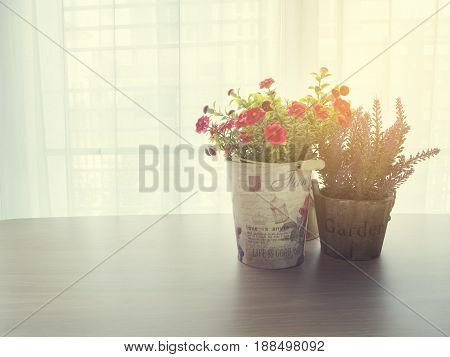wood office table with beautiful rose and purple lavender flower on flower pot over beautiful white drape window texture background.