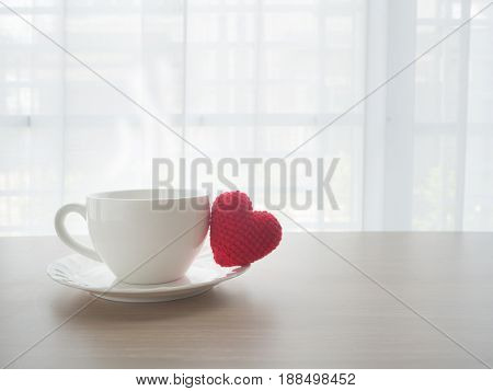 wood table with hot coffee cup and red heart shape symbol on blurry beautiful white drape window texture background.