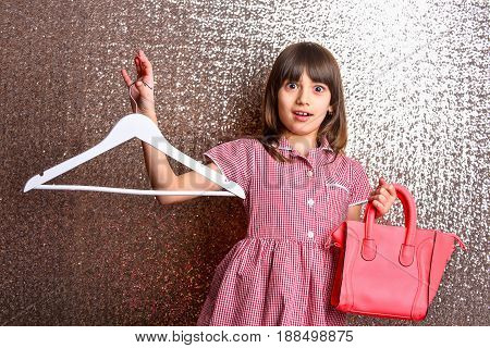 small pretty girl or cute fashionable child with long brunette hair and adorable smiling surprised happy face in checkered dress with female red leather bag and hanger on metallic silver background