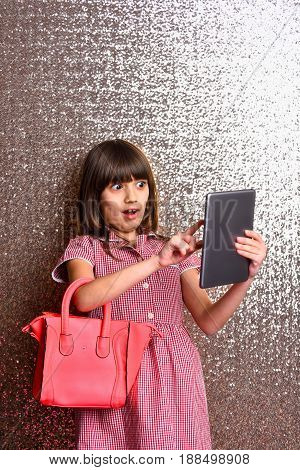 small pretty girl or cute fashionable child with long brunette hair and adorable surprised face in checkered dress with red leather bag and tablet on metallic silver background