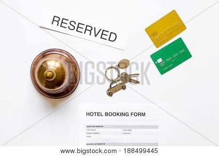 booking hotel room application form and keys on white desk background top view