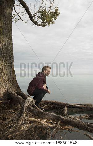 Young man kneeling beside lake and praying quietly