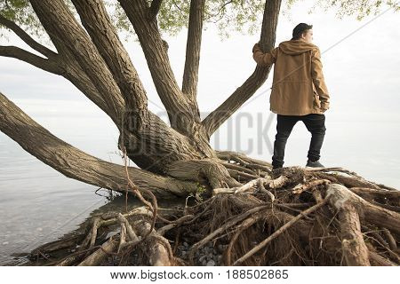 Young man standing near lake and pondering life beside trees