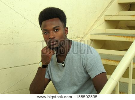 student man sitting in the staircase concrete walls
